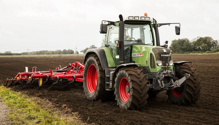 En traktor med harv på en åker.