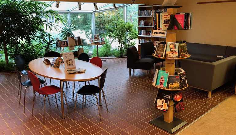 Bord och stolar, bokhylla, boksnurra och soffhörna i biblioteket.