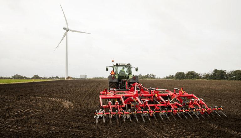 En traktor med harv sedd bakifrån på en åker med ett vindkraftverk i bakgrunden.