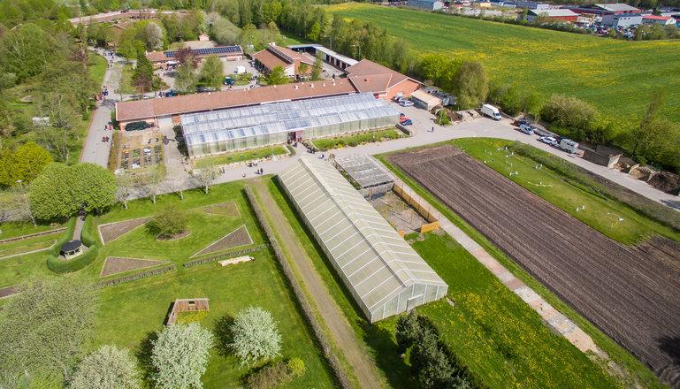 En del av Munkagårds trädgårdsanläggning med växthus, odlingsmark och park sett från ovan