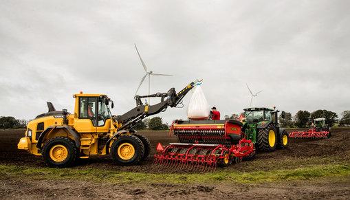 En hjullastare lyfter en säck utsäde för påfyllning i en såmaskin. Längre bort på åkern även en traktor med harv.