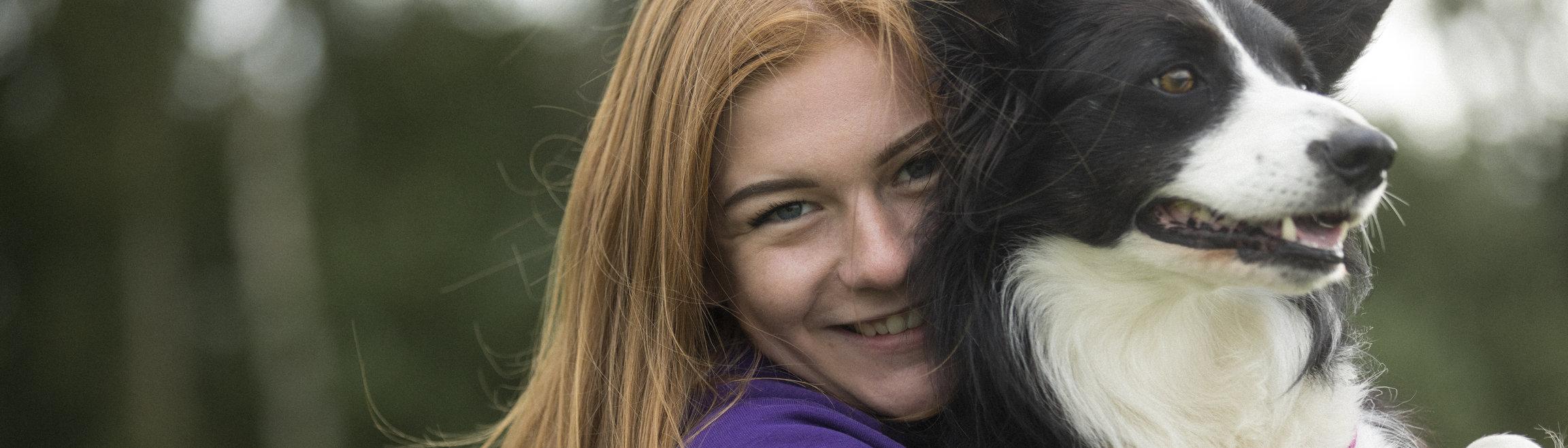 En leende tjej med en hund i famnen.