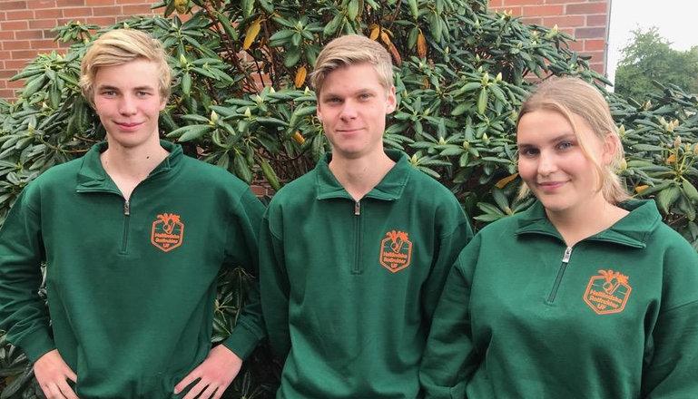 Tre elever i gröna tröjor med logotyp framför en buske