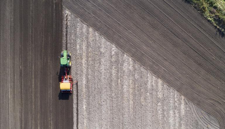 Flygbild med traktor som kör över en åker.