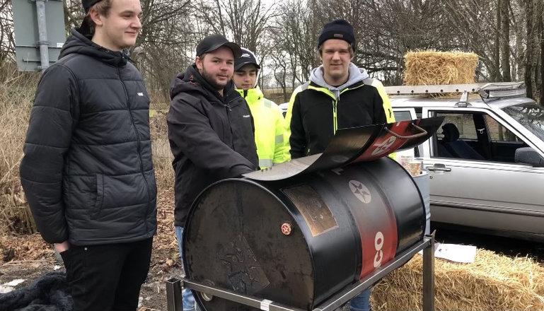 Fyra killar vid en grill tillverkad av ett oljefat.
