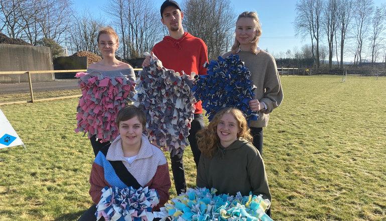 Fem elever poserar på en gräsmatta med sin UF-produkt.