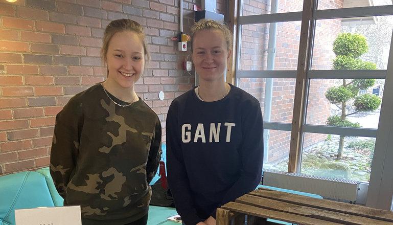 De två tjerna i uf-företaget ställer ut i skolans entré.