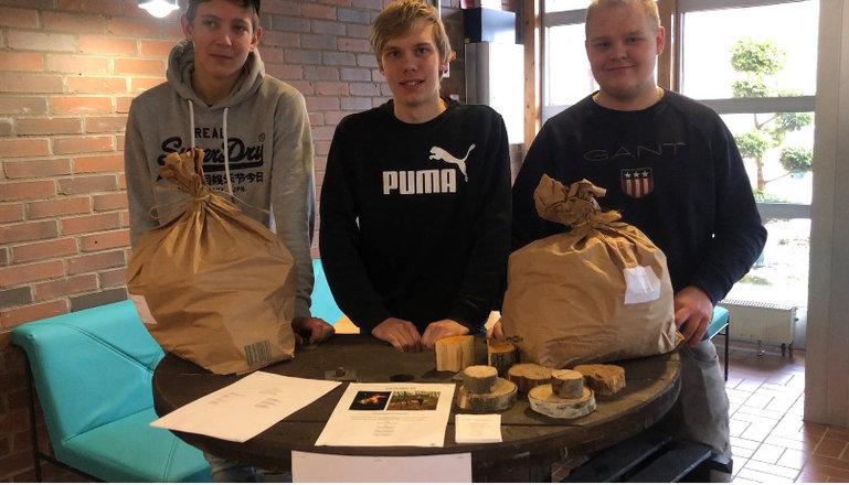Tre elever som visar upp sina träpuckar.
