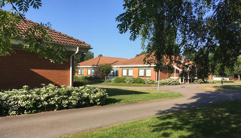 Ett hus på Munkagårdsgymnasiets elevboende sett utifrån med träd i förgrunden.