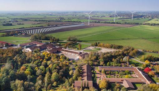 Munkagårdsgymnasiet sett från ovan, fält, vindkraftverk och längst bort hav och himmel.