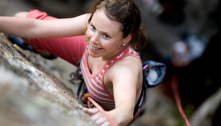 En kvninnlig klättrare på väg uppför en brant klippa sedd uppifrån.