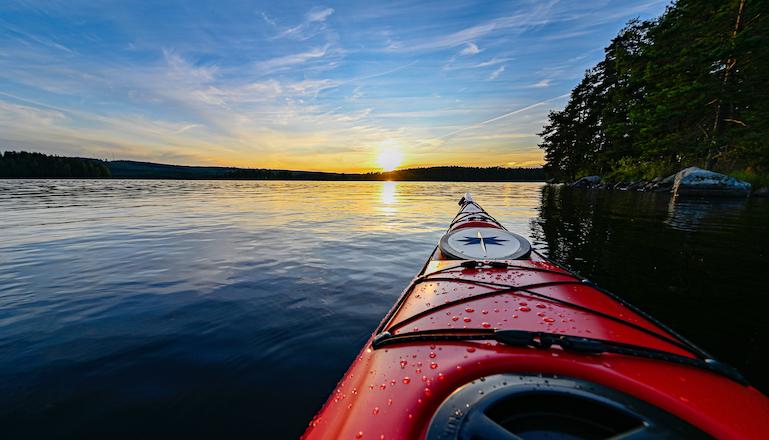 Fören på en röd kajak, vy ut över en sjö i solnedgång