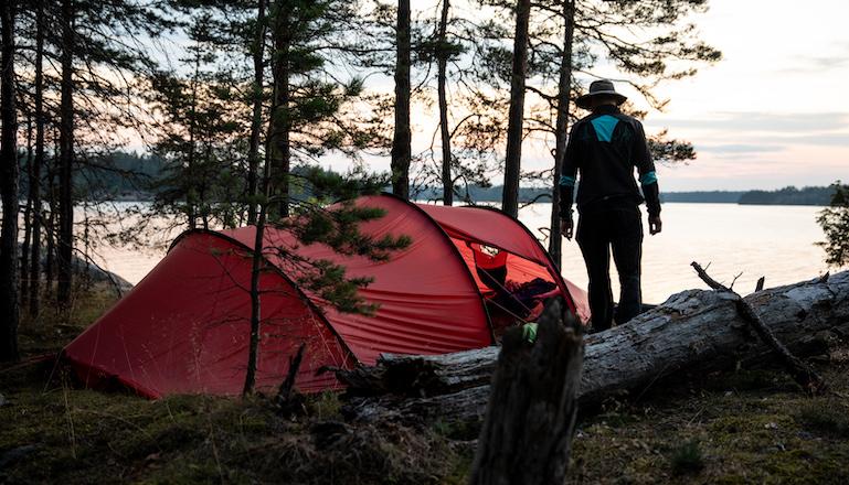 Ett rött tält och en person vid en skogsbeklädd strand vid havet.