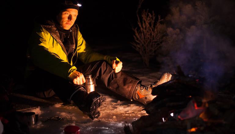 En kille med pannlampa sitter vid en brasa ute i snön i mörker.