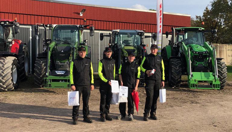 Fyra killar med diplom framför traktorer.