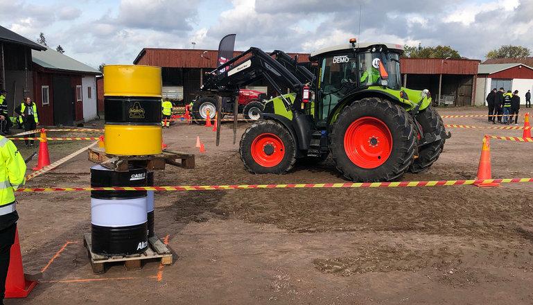 En traktor med pallgafflar utför ett tävlingsmoment med två staplade oljefat på lastpall.